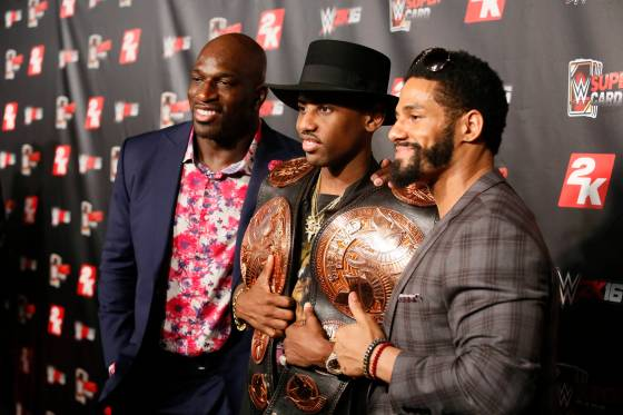 Hip-hop artist Fabolous holds the championship titles for current WWE Tag Team Champions The Prime Time Players, Titus OÕNeil, left, and Darren Young, right, at the WWE 2K SummerSlam Kickoff in New York, N.Y., Thursday, August 20, 2015. (Photo by Stuart Ramson/Invision for 2K/AP Images)