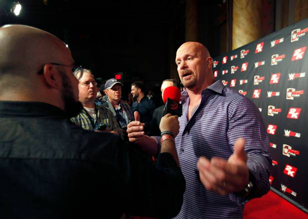 WWE Hall of Famer Stone Cold Steve Austin, right, and NXT Superstar Finn B‡lor, second from right, speak with media on the red carpet at the WWE 2K SummerSlam Kickoff in New York, N.Y., Thursday, August 20, 2015. (Photo by Stuart Ramson/Invision for 2K/AP Images)